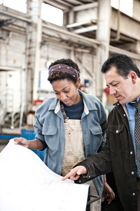 Hispanic man manager and black woman factory worker going over project plans in a sheet metal factorの写真素材 [FYI02262724]