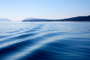Surface view of ocean with gentle waves, mountains in the distance.の写真素材 [FYI02262727]