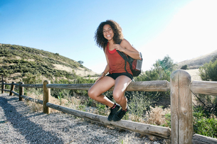 Young woman with curly brown hair hiking in urban park.の写真素材 [FYI02262732]