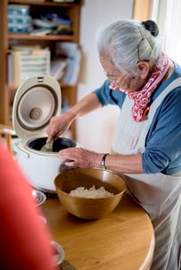 Elderly woman standing at a table in a kitchen, spooning sushi rice from rice cooker into bowl.の写真素材 [FYI02262733]
