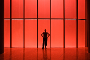 Businessman standing next to red tinted windows in an office lobby.の写真素材 [FYI02262737]
