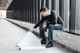 A Caucasian male architect working on building plans in a new raw business space.の写真素材 [FYI02262740]