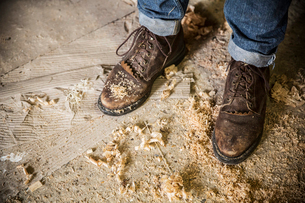 High angle view of a man wearing jeans and brown leather boots standing in a workshop, wood shavingsの写真素材 [FYI02262744]