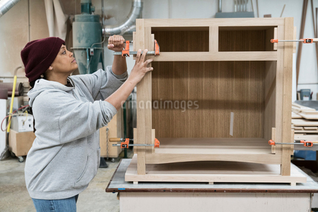 A Black woman carpenter working on a cabinet project in a large woodworking shop.の写真素材 [FYI02262750]