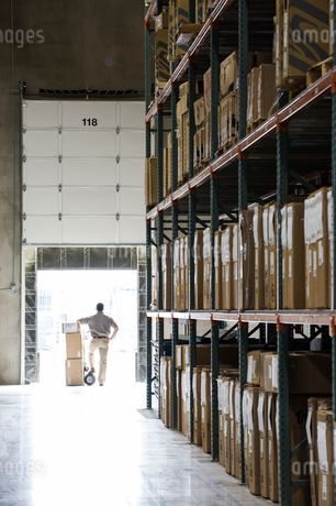 An employee with a hand truck full of boxes standing in a loading dock door in a large distributionの写真素材 [FYI02262759]