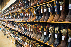 View of large selection of brown and black leather cowboy boots on shelves in a shoe shop.の写真素材 [FYI02262762]
