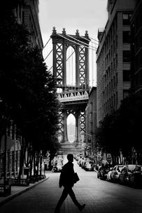 Man walking across narrow urban street, with Manhattan Bridge, New York, USA in the background.の写真素材 [FYI02262767]