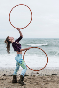 Young woman with brown hair and dreadlocks standing on a sandy beach by the ocean, balancing two hulの写真素材 [FYI02262771]