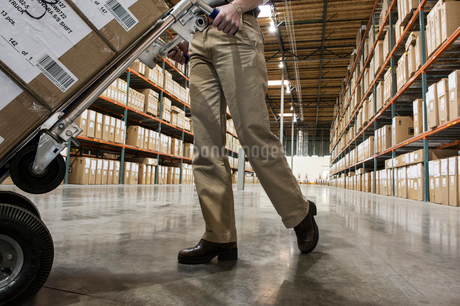 A low angle view looking up at a warehouse employee pushing a hand truck full of storage boxes downの写真素材 [FYI02262780]