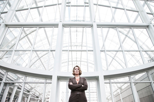 A portrait looking up at a Caucasian businesswoman standing next to a large graphic pattern on a winの写真素材 [FYI02262781]