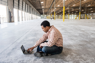 Black man working on lap top computer in front of loading dock doors in a new warehouse.の写真素材 [FYI02262787]