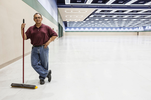 An Hispanic workman standing in a large interior space with a broom.の写真素材 [FYI02262792]