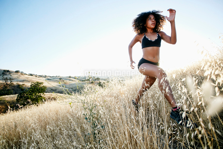 Young woman with curly brown hair running in urban park.の写真素材 [FYI02262797]