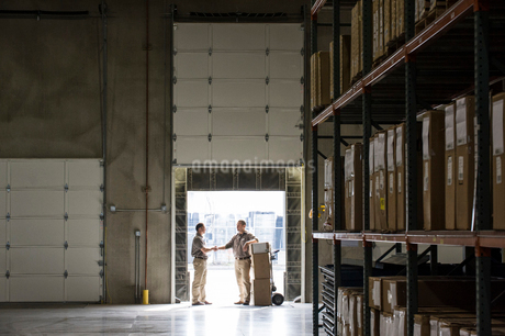 Two warehouse workers shaking hands while standing in the doorway of a loading dock in a large distrの写真素材 [FYI02262802]