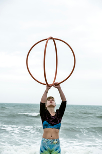Young woman with brown hair and dreadlocks standing by the ocean, balancing two hula hoops.の写真素材 [FYI02262810]