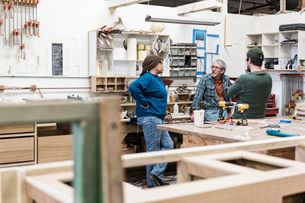 A group of mixed race carpenters discussing a project at a work station in a large woodworking shop.の写真素材 [FYI02262820]
