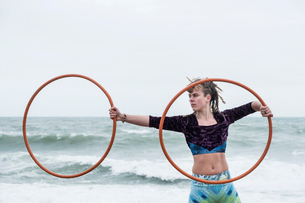 Young woman with brown hair and dreadlocks standing by the ocean, balancing two hula hoops.の写真素材 [FYI02262821]