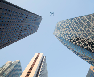 Low angle view from urban street towards clear sky, along glass and steel facades of tall skyscraperの写真素材 [FYI02262830]