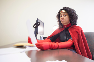Portrait of a black businesswoman office super hero sitting at her office computer.の写真素材 [FYI02262839]