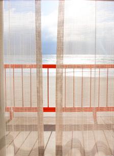 View trough gauze curtain onto balcony over sandy beach and ocean.の写真素材 [FYI02262841]