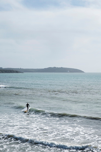 Surfer wearing wet suit riding ocean wave close to shore.の写真素材 [FYI02262843]