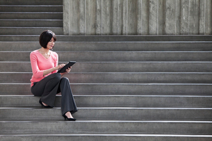 Hispanic businesswoman working on a notebook computer while sitting on steps in a convention centre.の写真素材 [FYI02262844]