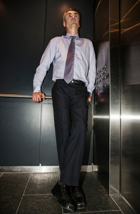 Caucasian businessman standing in the corner of an elevator in a large office building.の写真素材 [FYI02262845]
