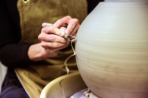 Close up of potter wearing apron working on spherical clay vase on pottery wheel.の写真素材 [FYI02262847]