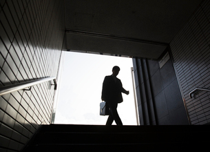 Low angle view of man carrying briefcase entering entrance to subway station.の写真素材 [FYI02262849]