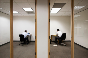 A view of two businessmen working on opposite sides of a wall in two different office spaces.の写真素材 [FYI02262850]