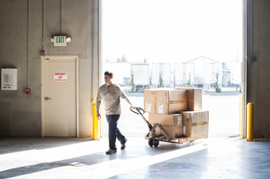 A male warehouse worker moving boxes of products using a manual pallet jack.の写真素材 [FYI02262853]