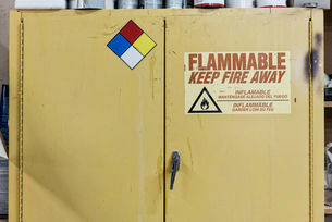 Safety sign reminders mounted to a metal cabinet in a woodworking factory.の写真素材 [FYI02262856]