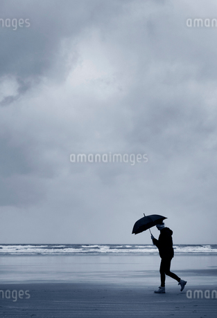 Side view of man carrying umbrella walking along sandy beach by ocean under stormy sky.の写真素材 [FYI02262857]