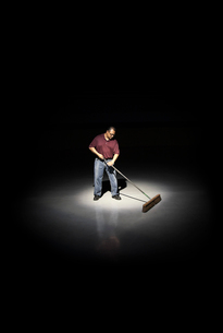 A man with a broom working in an area of a floor lit up by a spotlight.の写真素材 [FYI02262859]