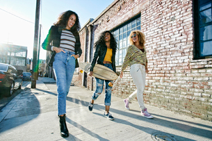 Three young women with long curly hair walking along pavement, one carrying skateboard.の写真素材 [FYI02262864]