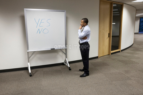 A black businessman thinking and standing in front of an office white board with the words Yes and Nの写真素材 [FYI02262865]