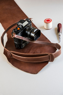 High angle close up of a vintage camera with handmade brown leather strap.の写真素材 [FYI02262871]