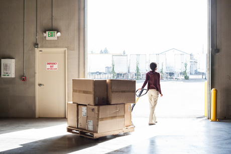 A female warehouse worker moving products in cardboard boxes by using a manual pallet jack in a distの写真素材 [FYI02262872]