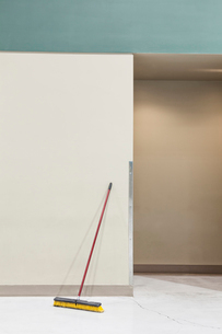 A still life view of a broom leaning up against a wall.の写真素材 [FYI02262873]