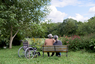 Husband and wife, rear view of elderly man wearing hat and woman sitting side by side on a bench inの写真素材 [FYI02262877]