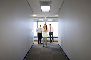 A portrait of a mixed group of business people standing at the end of a long hallway.の写真素材 [FYI02262879]
