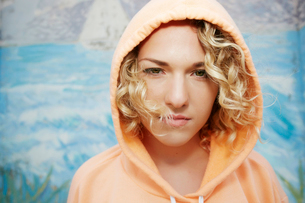 Portrait of woman with curly blond hair wearing pink hoodie, looking at camera.の写真素材 [FYI02262881]