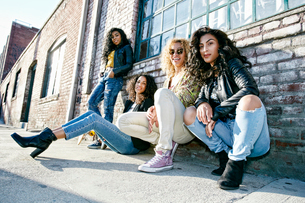 Four young women with curly hair sitting side by side on steps outside a building.の写真素材 [FYI02262882]