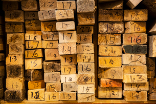 Close up of large selection of wooden planks stacked on shelves in a warehouse.の写真素材 [FYI02262886]