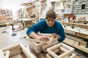 A Black woman carpenter working on a cabinet project in a large woodworking shop.の写真素材 [FYI02262890]