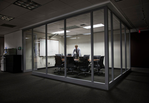 Caucasian businessman working at night in a glassed in conference room.の写真素材 [FYI02262905]