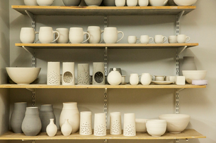 Racks of hand thrown hand crafted pottery vases and objects on shelves in the drying room.の写真素材 [FYI02262918]