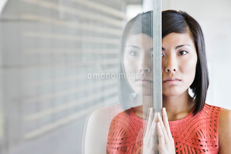 An Asian businesswoman reflected on a glass wall in an office lobby.の写真素材 [FYI02262923]