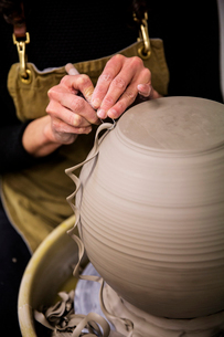 Close up of potter wearing apron working on spherical clay vase on pottery wheel.の写真素材 [FYI02262935]