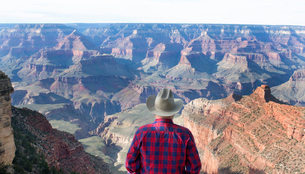 Rear view of man wearing checkered shirt and cowboy hat standing on top of canyon, looking at view.の写真素材 [FYI02262936]